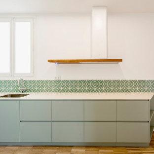 Immagine di una cucina design di medie dimensioni con lavello sottopiano, ante lisce, ante turchesi, paraspruzzi verde, paraspruzzi con piastrelle di cemento, pavimento in legno massello medio, nessuna isola, pavimento multicolore e top bianco
