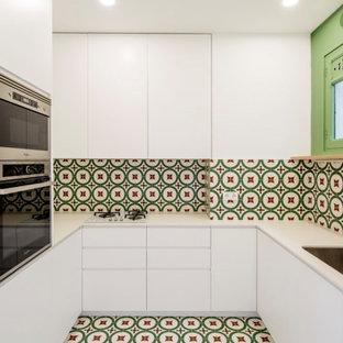 バルセロナの小さいエクレクティックスタイルのおしゃれなキッチン (アンダーカウンターシンク、フラットパネル扉のキャビネット、白いキャビネット、タイルカウンター、マルチカラーのキッチンパネル、セメントタイルのキッチンパネル、シルバーの調理設備、セメントタイルの床、アイランドなし、マルチカラーの床、白いキッチンカウンター) の写真