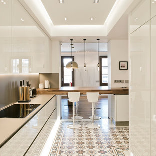 Inspiration for a large contemporary u-shaped open plan kitchen in Barcelona with a drop-in sink, flat-panel cabinets, white cabinets, quartz benchtops, brown splashback, panelled appliances, cement tiles, with island, multi-coloured floor and brown benchtop.