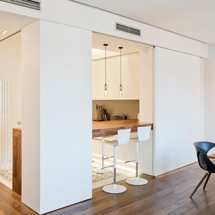 Photo of a large contemporary u-shaped open plan kitchen in Barcelona with a drop-in sink, flat-panel cabinets, white cabinets, quartz benchtops, brown splashback, panelled appliances, cement tiles, with island, multi-coloured floor and brown benchtop.