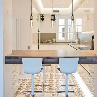 Foto de cocina contemporánea, grande, con armarios con paneles lisos, puertas de armario blancas, encimera de cuarzo compacto, suelo de azulejos de cemento, suelo multicolor, salpicadero verde y encimeras grises