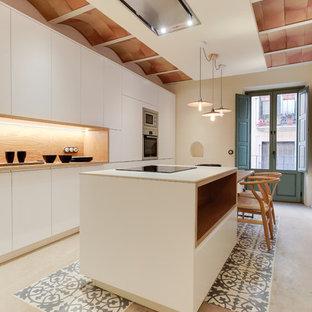 他の地域の大きい地中海スタイルのおしゃれなキッチン (フラットパネル扉のキャビネット、白いキャビネット、シルバーの調理設備の、マルチカラーの床、木材のキッチンパネル) の写真