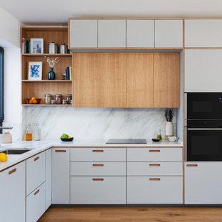 Пример оригинального дизайна: угловая кухня-гостиная среднего размера в современном стиле с врезной раковиной, фасадами в стиле шейкер, светлыми деревянными фасадами, гранитной столешницей, серым фартуком, фартуком из гранита, техникой под мебельный фасад, паркетным полом среднего тона, коричневым полом и серой столешницей без острова