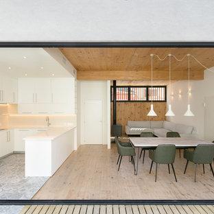 Modelo de cocina en U, contemporánea, abierta, con armarios con paneles lisos, puertas de armario blancas, electrodomésticos de acero inoxidable, península, suelo gris y encimeras blancas