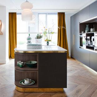 Diseño de cocina comedor de galera, actual, con armarios con paneles lisos, puertas de armario azules, electrodomésticos con paneles, suelo de madera en tonos medios, una isla, suelo marrón y encimeras blancas