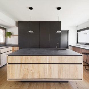 Ejemplo de cocina en U, minimalista, con fregadero bajoencimera, armarios con paneles lisos, puertas de armario de madera clara, suelo de madera clara, una isla, suelo beige y encimeras negras
