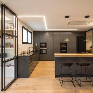 Foto de cocina en L, actual, grande, abierta, con armarios con paneles lisos, puertas de armario negras, península, fregadero bajoencimera, salpicadero blanco, electrodomésticos negros y suelo de madera clara
