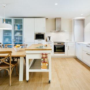 Imagen de cocina tradicional renovada con puertas de armario blancas, salpicadero blanco, electrodomésticos de acero inoxidable, una isla y encimeras blancas