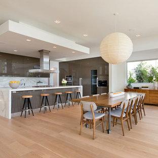 Foto de cocina en L, actual, abierta, con armarios con paneles lisos, salpicadero blanco, suelo de madera clara, encimeras blancas, puertas de armario grises, una isla y suelo beige