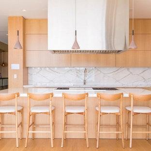 Ejemplo de cocina lineal, contemporánea, grande, con fregadero bajoencimera, armarios con paneles lisos, puertas de armario de madera clara, encimera de cuarzo compacto, salpicadero blanco, suelo de madera en tonos medios, una isla, encimeras blancas y suelo marrón