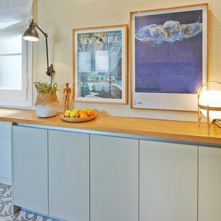 Ejemplo de cocina actual con armarios con paneles lisos, puertas de armario grises, encimera de madera, suelo de baldosas de cerámica y suelo gris
