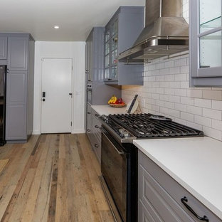 Inspiration for a large industrial u-shaped kitchen/diner in Los Angeles with a single-bowl sink, beaded cabinets, grey cabinets, quartz worktops, white splashback, metro tiled splashback, black appliances, plywood flooring, no island, multi-coloured floors and white worktops.