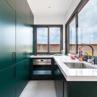 Modelo de cocina contemporánea, sin isla, con fregadero bajoencimera, armarios con paneles lisos, puertas de armario verdes, salpicadero de vidrio, electrodomésticos de acero inoxidable, suelo blanco y encimeras blancas