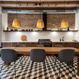 Ejemplo de cocina comedor lineal, industrial, con armarios con paneles lisos, puertas de armario de madera en tonos medios, salpicadero blanco, salpicadero de azulejos tipo metro, electrodomésticos negros y suelo multicolor