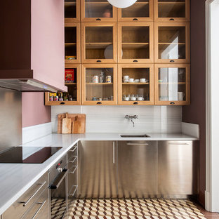 Design ideas for a transitional l-shaped kitchen in Barcelona with an undermount sink, stainless steel cabinets, white splashback, stainless steel appliances, white benchtop, flat-panel cabinets, stone slab splashback and brown floor.