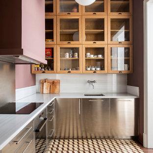 Inredning av ett klassiskt vit vitt l-kök, med en undermonterad diskho, skåp i rostfritt stål, vitt stänkskydd, rostfria vitvaror, släta luckor, stänkskydd i sten och brunt golv