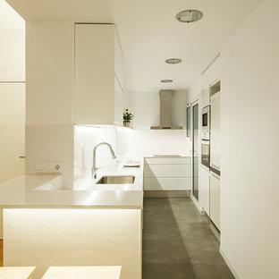 Modelo de cocina en L, contemporánea, de tamaño medio, abierta, con fregadero bajoencimera, armarios con paneles lisos, puertas de armario blancas, encimera de cuarzo compacto, salpicadero blanco, electrodomésticos blancos, suelo de baldosas de cerámica y suelo gris