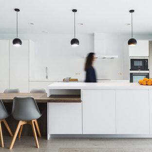Ejemplo de cocina lineal, escandinava, con puertas de armario blancas, salpicadero blanco, una isla, encimeras blancas, armarios con paneles lisos y suelo de madera clara