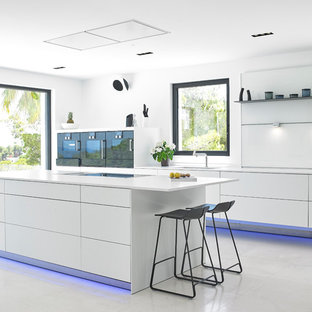Ejemplo de cocina de galera, actual, con armarios con paneles lisos, puertas de armario blancas, una isla, suelo blanco y encimeras blancas