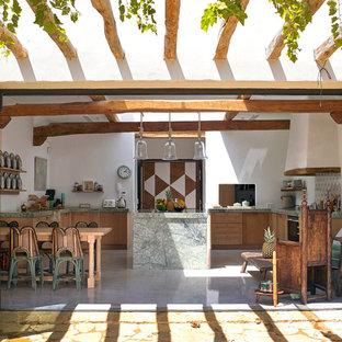 Aménagement d'une cuisine américaine exotique en U avec un placard à porte shaker, des portes de placard en bois brun, un îlot central, un sol gris et un plan de travail gris.