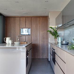 ロンドンのコンテンポラリースタイルのおしゃれなアイランドキッチン (フラットパネル扉のキャビネット、ベージュのキャビネット、白いキッチンパネル、ガラス板のキッチンパネル、黒い調理設備、グレーの床、白いキッチンカウンター) の写真