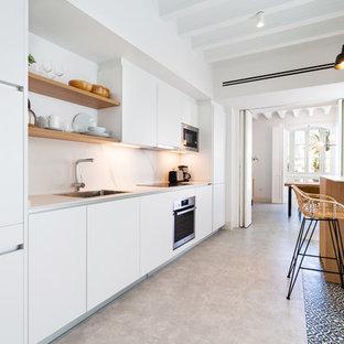 Imagen de cocina lineal, actual, con fregadero encastrado, armarios con paneles lisos, puertas de armario blancas, electrodomésticos de acero inoxidable, suelo gris y encimeras blancas