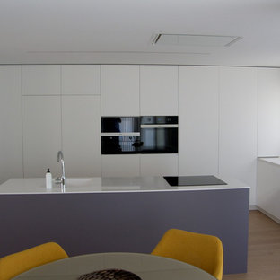 Inspiration for a mid-sized contemporary l-shaped open plan kitchen in Palma de Mallorca with a single-bowl sink, recessed-panel cabinets, white cabinets, quartz benchtops, white splashback, marble splashback, panelled appliances, light hardwood floors, with island, beige floor and orange benchtop.