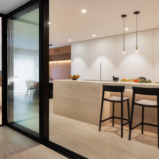 Design ideas for a modern single-wall open plan kitchen in Alicante-Costa Blanca with flat-panel cabinets, white cabinets, limestone benchtops, limestone floors, with island, brown floor and brown benchtop.