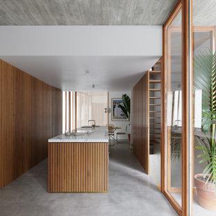 バルセロナの広いインダストリアルスタイルのおしゃれなキッチン (アンダーカウンターシンク、レイズドパネル扉のキャビネット、中間色木目調キャビネット、大理石カウンター、パネルと同色の調理設備、コンクリートの床、グレーの床、白いキッチンカウンター) の写真