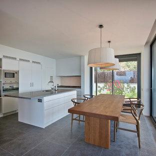 Modelo de cocina comedor en L, moderna, con fregadero bajoencimera, armarios con paneles lisos, puertas de armario blancas, electrodomésticos de acero inoxidable, una isla, suelo gris y encimeras grises