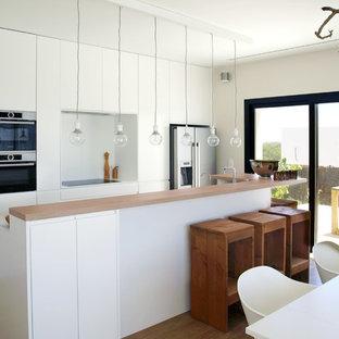 Modelo de cocina comedor minimalista con electrodomésticos de acero inoxidable, suelo de madera en tonos medios, encimeras blancas, una isla, armarios con paneles lisos, puertas de armario blancas y salpicadero blanco