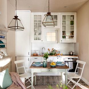 マドリードの小さいシャビーシック調のおしゃれなLDK (無垢フローリング、ガラス扉のキャビネット、白いキャビネット、木材カウンター、白いキッチンパネル、アイランドなし) の写真