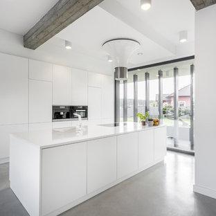 Ejemplo de cocina de galera, minimalista, con armarios con paneles lisos, puertas de armario blancas, suelo de cemento, una isla, suelo gris y encimeras blancas