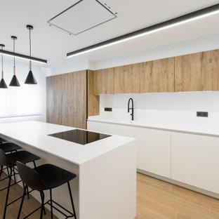 Diseño de cocina de galera, moderna, con armarios con paneles lisos, puertas de armario de madera oscura, suelo de madera en tonos medios, una isla, suelo marrón y encimeras blancas