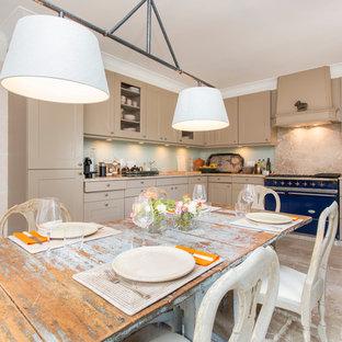 Modelo de cocina comedor en L, campestre, sin isla, con armarios con paneles empotrados, puertas de armario beige, salpicadero beige y electrodomésticos de colores