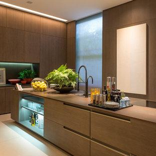 Ejemplo de cocina lineal, moderna, grande, abierta, con armarios con paneles lisos, puertas de armario de madera clara, una isla y suelo beige
