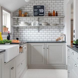 Пример оригинального дизайна: маленькая отдельная, параллельная кухня в современном стиле с раковиной в стиле кантри, фасадами с утопленной филенкой, серыми фасадами, белым фартуком, фартуком из плитки кабанчик и деревянным полом без острова