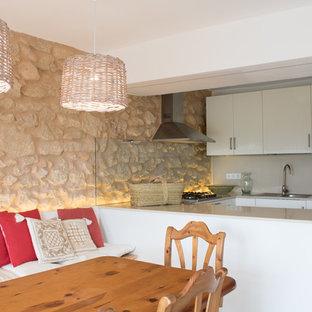 バレンシアの地中海スタイルのおしゃれなキッチン (ドロップインシンク、フラットパネル扉のキャビネット、白いキャビネット、ベージュキッチンパネル、ガラス板のキッチンパネル、ベージュのキッチンカウンター) の写真