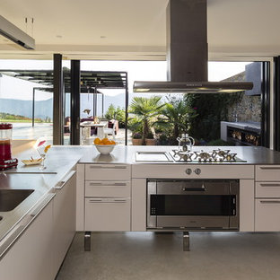 Photo of a large industrial l-shaped open plan kitchen in Barcelona with an integrated sink, flat-panel cabinets, white cabinets, stainless steel benchtops, stainless steel appliances, concrete floors and no island.