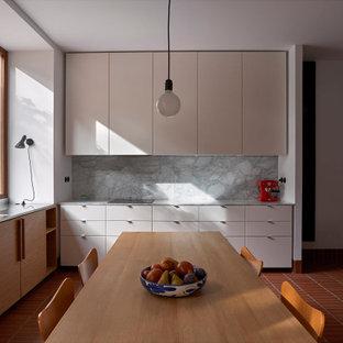 Ejemplo de cocina comedor en L, mediterránea, sin isla, con fregadero bajoencimera, armarios con paneles lisos, puertas de armario beige, salpicadero verde, suelo rojo y encimeras grises