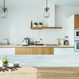 マドリードの北欧スタイルのおしゃれなキッチン (一体型シンク、フラットパネル扉のキャビネット、中間色木目調キャビネット、木材カウンター、白いキッチンパネル、サブウェイタイルのキッチンパネル、白い調理設備、淡色無垢フローリング、茶色い床、ベージュのキッチンカウンター) の写真