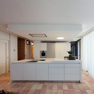 Foto de cocina lineal, actual, abierta, con armarios con paneles lisos, puertas de armario blancas, una isla, encimeras blancas, fregadero encastrado, suelo de baldosas de terracota y suelo rojo