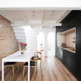Ejemplo de cocina comedor lineal, actual, con armarios con paneles lisos, puertas de armario negras, encimera de madera, salpicadero de vidrio y suelo de madera clara