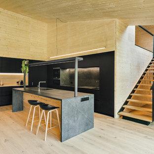 Ejemplo de cocina en L, minimalista, abierta, con fregadero integrado, armarios con paneles lisos, puertas de armario negras, salpicadero negro, electrodomésticos negros, suelo de madera clara, una isla y encimeras negras