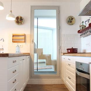 Modelo de cocina de galera, tradicional renovada, pequeña, con puertas de armario blancas, suelo de madera en tonos medios, encimeras marrones, armarios con paneles con relieve, encimera de madera, salpicadero blanco, salpicadero de azulejos tipo metro, península y suelo marrón