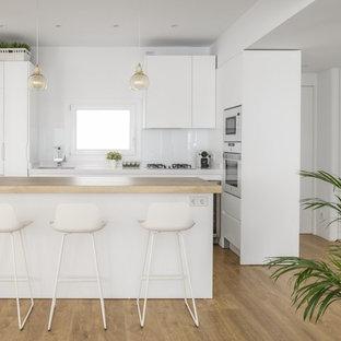 他の地域のコンテンポラリースタイルのおしゃれなキッチン (フラットパネル扉のキャビネット、白いキャビネット、木材カウンター、白いキッチンパネル、白い調理設備、アンダーカウンターシンク、ガラス板のキッチンパネル、淡色無垢フローリング、茶色い床、ベージュのキッチンカウンター) の写真