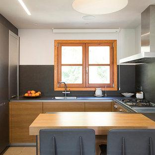 Modelo de cocina en U, contemporánea, pequeña, abierta, con armarios con paneles lisos, puertas de armario de madera oscura, salpicadero negro, electrodomésticos de acero inoxidable, suelo beige y península