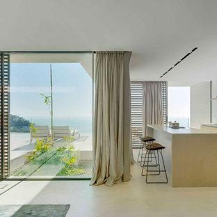 Imagen de cocina minimalista con puertas de armario de madera clara, electrodomésticos con paneles, una isla y suelo beige