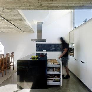 Imagen de cocina comedor actual, de tamaño medio, con armarios con paneles lisos, puertas de armario blancas, encimera de granito, suelo de cemento, una isla, suelo gris y encimeras negras