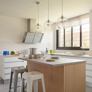 マドリードの中くらいのエクレクティックスタイルのおしゃれなキッチン (シングルシンク、フラットパネル扉のキャビネット、白いキャビネット、ベージュキッチンパネル、人工大理石カウンター、セラミックタイルの床、グレーのキッチンカウンター) の写真